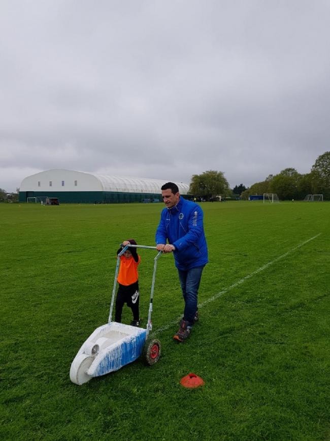 Marking the pitch - Tiptree Jobserve chairman and secretary Jonathan Dalton gets a helping hand as he works on the pitch at Warriors Rest