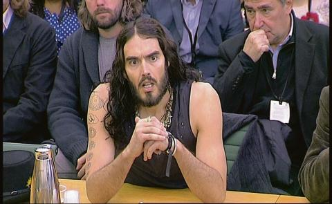 Russell Brand speaks before the committee