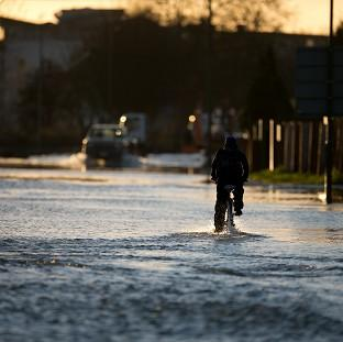 Thurrock Gazette: A man cycles down a flooded road in Chertsey, Surrey