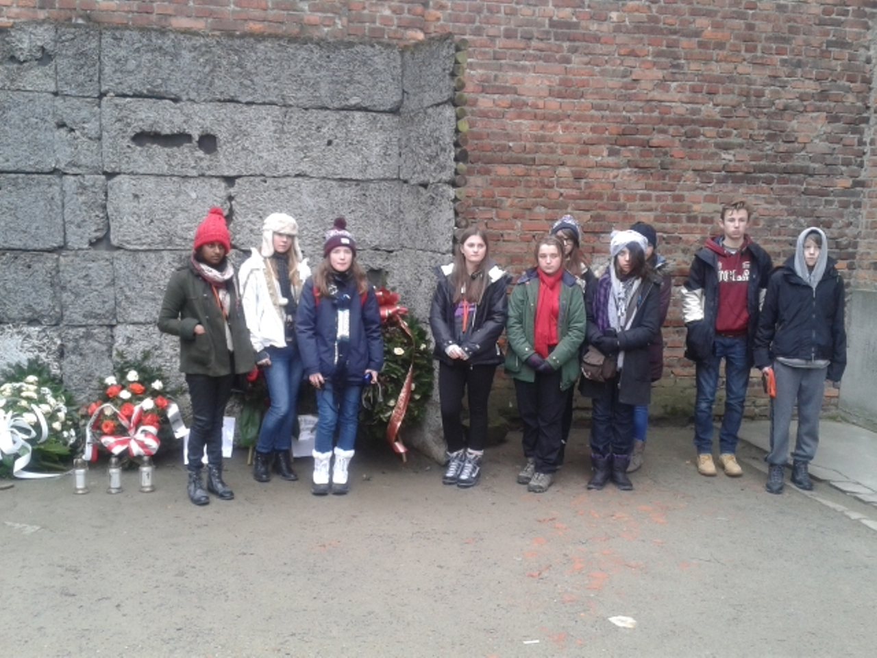 Young people from Thurrock line up next to the Firing Wall memorial in Auschwitz