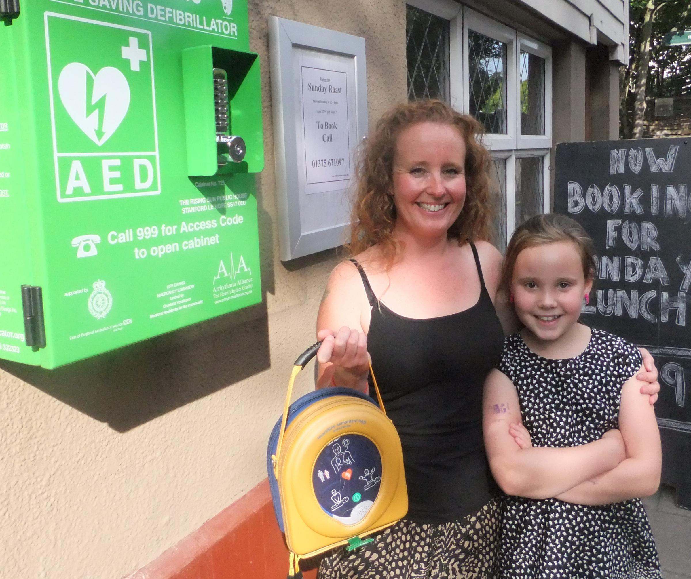 Charlotte and her daughter Katie with the defibrillator at the Rising Sun pub in Stanford-le-Hope.