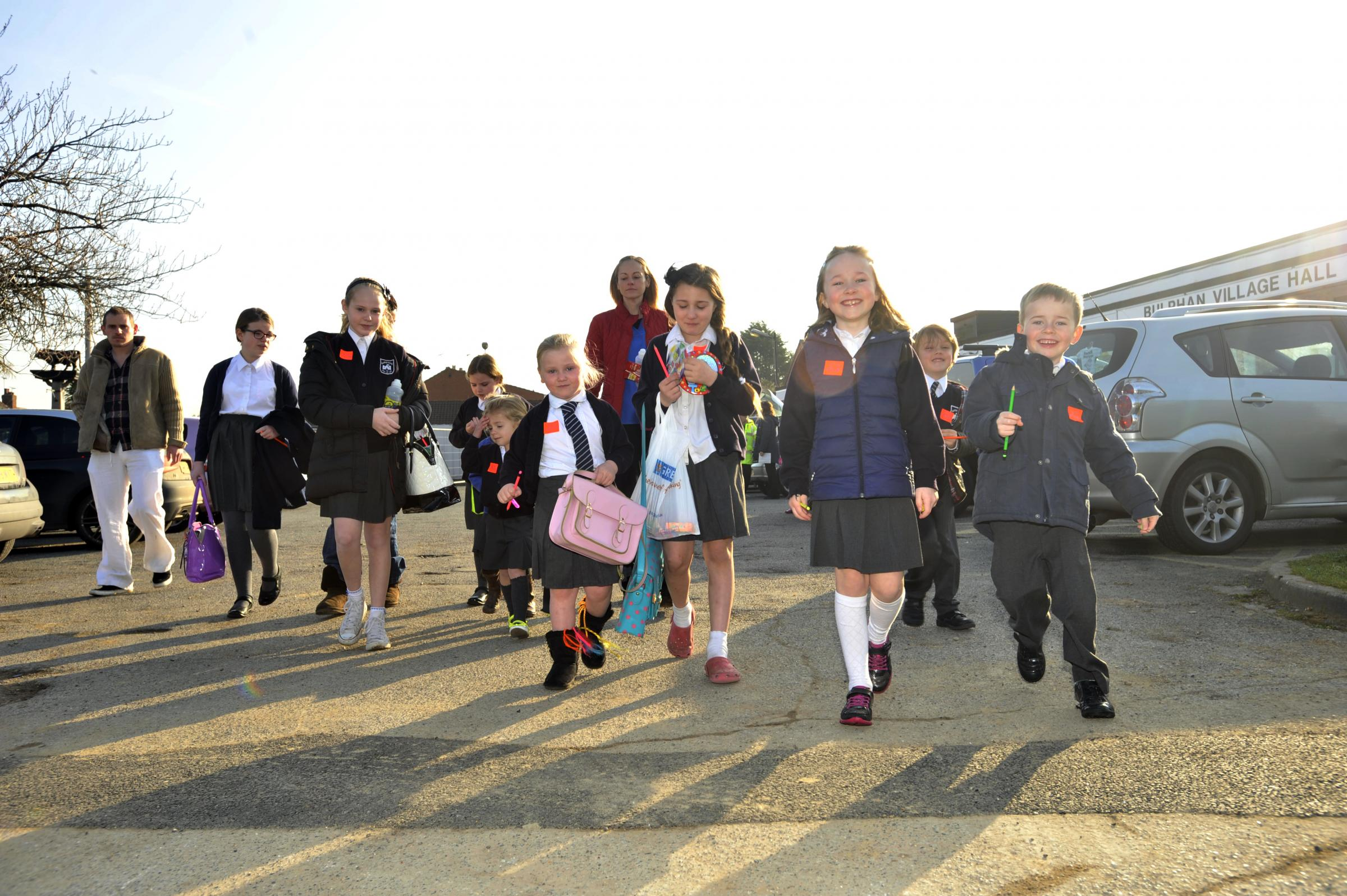 Bulphan Primary School pupils walk to school after their parents have parked up at the village hall down the road