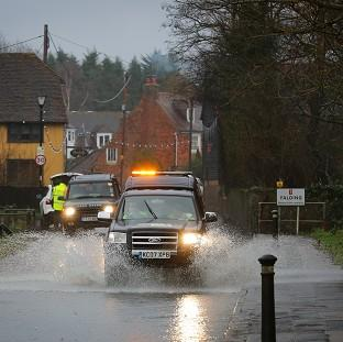 Thurrock Gazette: A car passes through a flooded road in Yalding, Kent