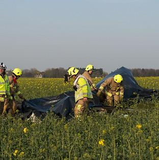 Emergency services at the scene of a plane crash near Ongar, Essex, where a Yak 52 aircraft's pilot and passenger, both from Essex, were killed after the plane flew out from North Weald airfield.