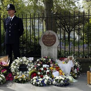 Thurrock Gazette: A police officer stands beside floral tributes during a memorial service held in St James Square, London, to mark the thirtieth anniversary of the death of WPC Yvonne Fletcher